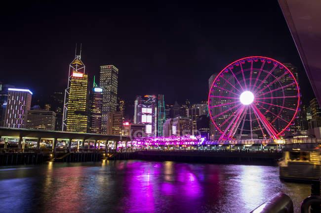 Hong Kong, centro, ciudad con rueda de Ferris por la noche - foto de stock
