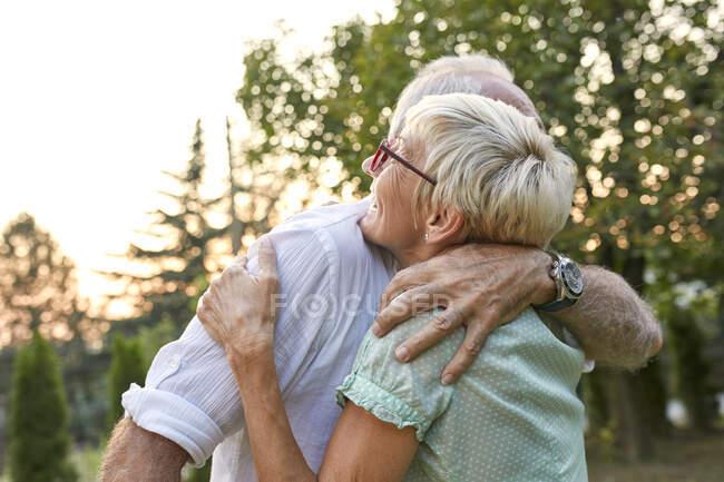 Felice coppia anziana abbracci all'aperto — Foto stock