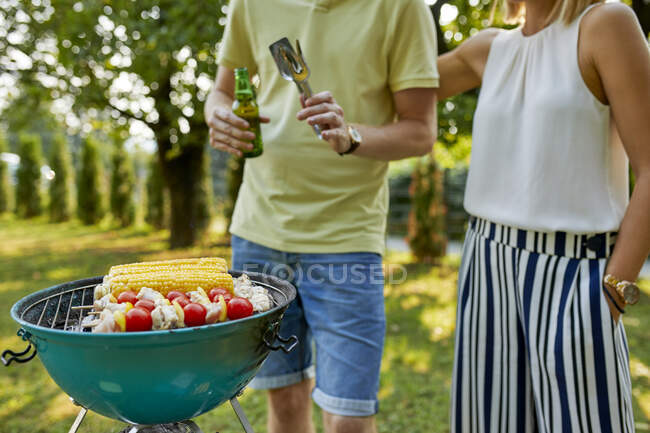 Young couple having a barbecue in garden — Stock Photo