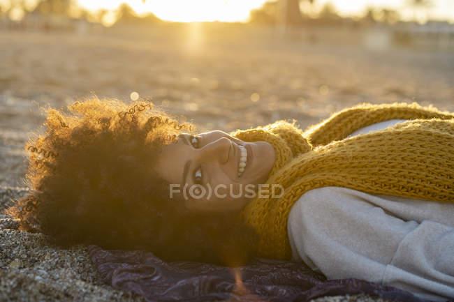 Mulher deitada na areia, relaxando na praia — Fotografia de Stock