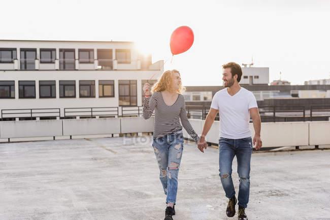 Счастливая молодая пара на террасе на крыше в вечерние сумерки — стоковое фото