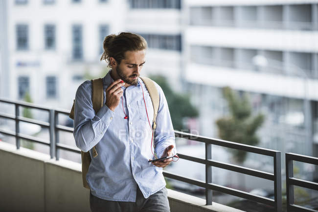 Young businessman walking in parking garage, using smartphone — Stock Photo