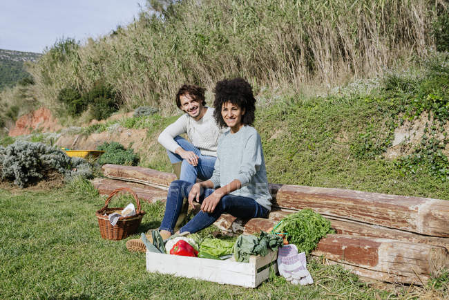 Paar sitzt in seinem Gemüsegarten und picknickt nach der Ernte — Stockfoto