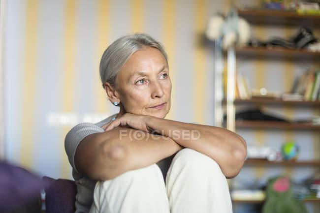 Porträt einer nachdenklichen Seniorin, die zu Hause auf der Couch sitzt — Stockfoto