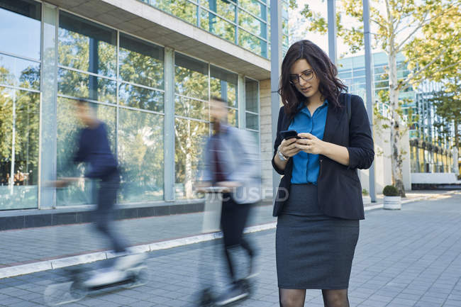 Бизнесмен пользуется мобильным телефоном, а пассажиры едут на скутерах. — стоковое фото