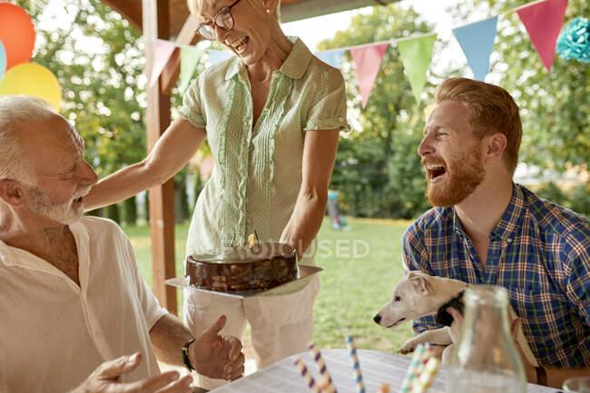 Счастливая женщина вручает торт на садовом празднике — стоковое фото
