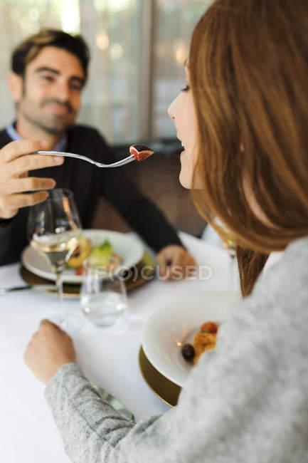 MMan дозволяючи жінці смак їжі в ресторані — стокове фото