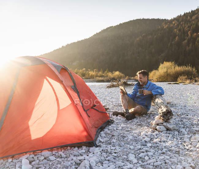Mature man camping at riverside, using tablet — Foto stock