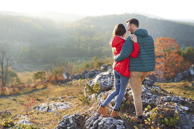 Rear view of couple on a hiking trip in the mountains standing on rock — Stock Photo