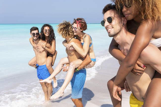 Amici che camminano sulla spiaggia, portando ragazze a cavalluccio — Foto stock