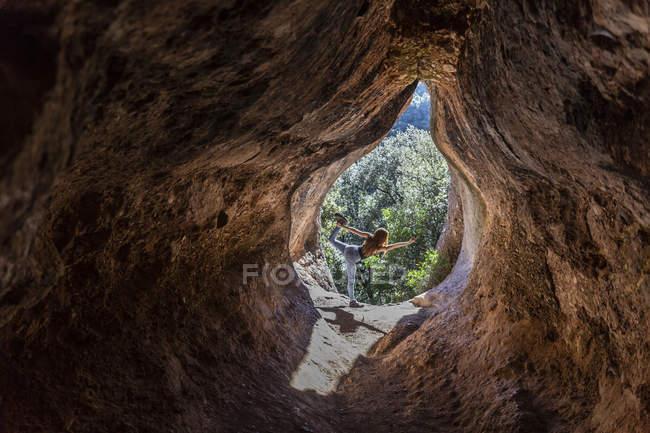 Молода жінка практикує йогу в печерному вході (Кова - Сіманья, Барселона, Іспанія). — стокове фото