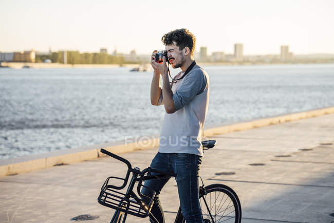 Young man with commuter fixie bike taking a picture at the riverside — Stock Photo