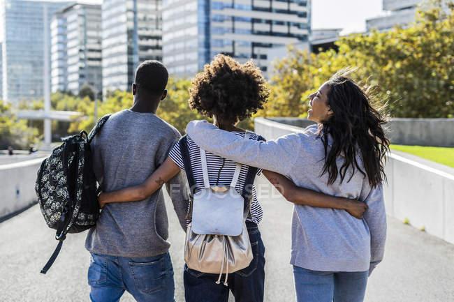 Tre amici che esplorano la città, camminano per strada, a braccetto — Foto stock