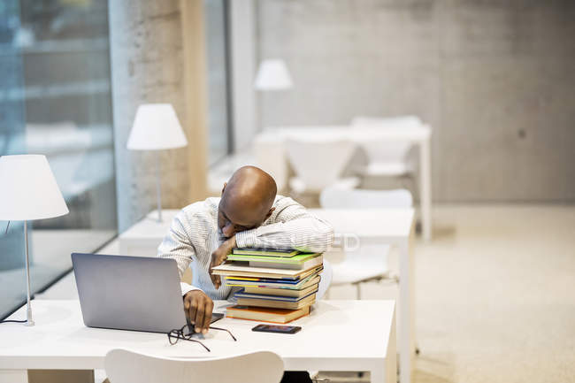 Exhausted mature man sitting at desk leaning on stack of books — Stock Photo