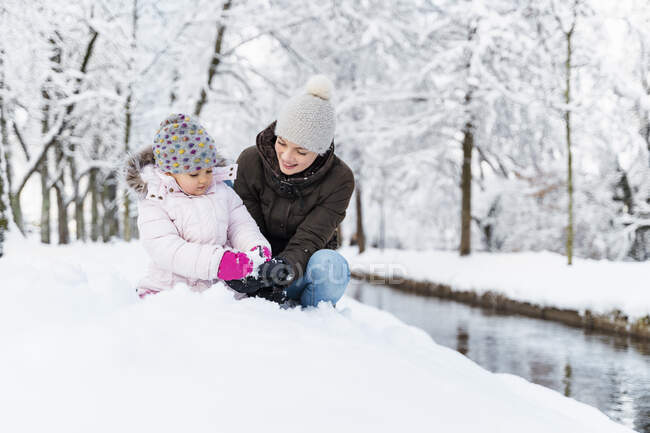 Happy mother with daughter at a moat in winter landscape — Stock Photo