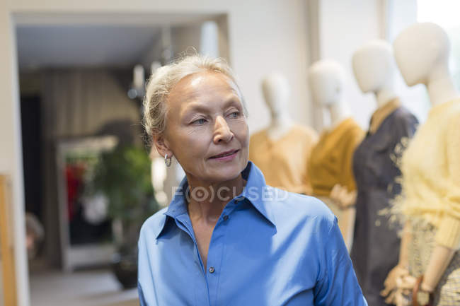 Усміхнена старша жінка в бутік озираючись навколо — стокове фото
