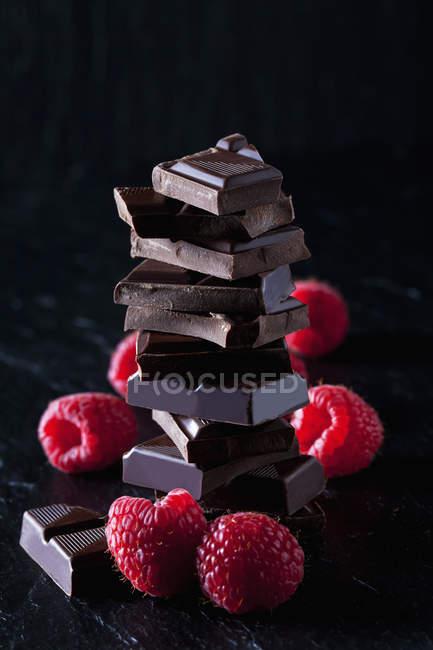 Купа шоколадних шматочків і малини на чорному шифері — стокове фото