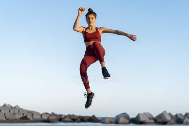 Молодая женщина во время тренировки, прыжки — стоковое фото