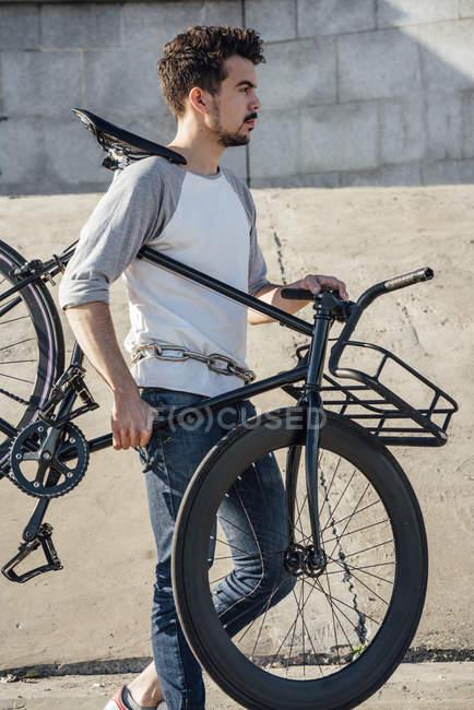 Молодий чоловік проведення приміського велосипеда fixie на бетонній стіні — стокове фото