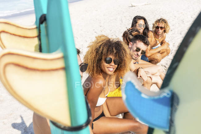 Jóvenes surfistas tomando un descanso, sentados en la playa - foto de stock