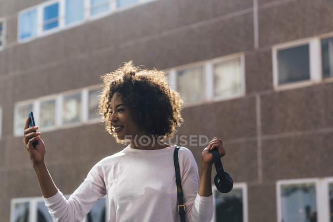 Молода ділова жінка, яка користується смартфоном у місті. — стокове фото