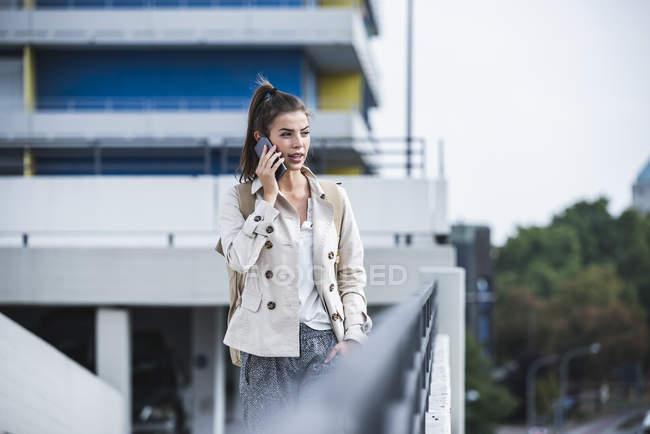 Jovem empresária usando smartphone na cidade — Fotografia de Stock