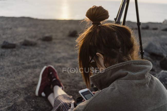 Spain, Canary Islands, Fuerteventura, young woman using smartphone and digital camera — стокове фото