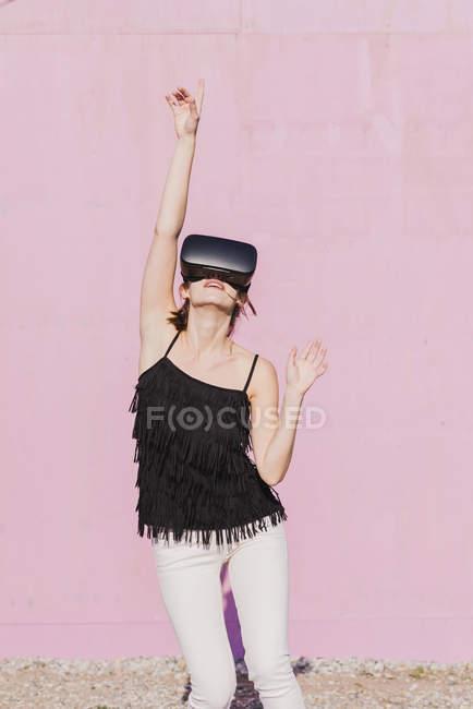 Junge Frau mit Vr-Brille bewegt sich vor rosa Wand — Stockfoto