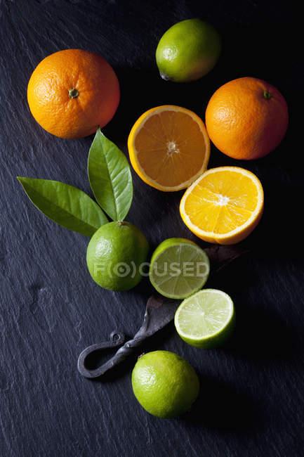 Нарізані Лайми і апельсини з старим ножем — стокове фото