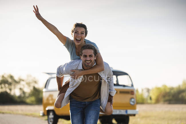 Happy couple doing a road trip with a camper, pretending to fly on the road — Stock Photo