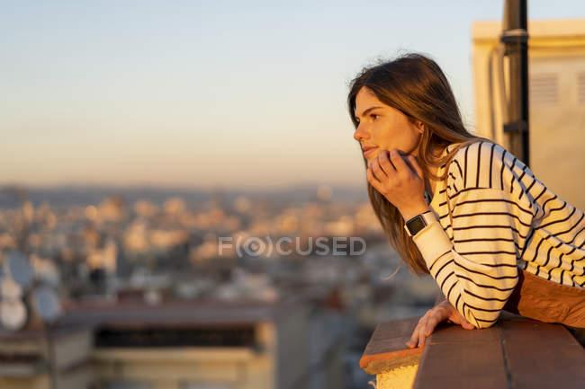 Giovane donna che si rilassa sulla terrazza sul tetto al tramonto — Foto stock