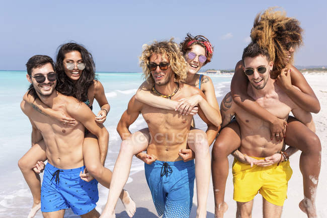 Amigos andando na praia, carregando namoradas piggyback — Fotografia de Stock