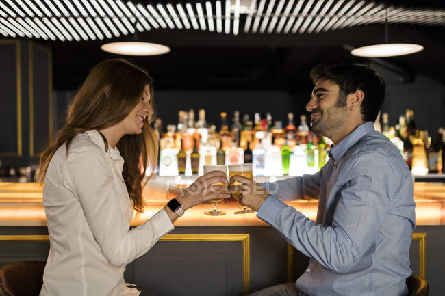 Smiling couple clinking beer glasses in a bar — Stock Photo