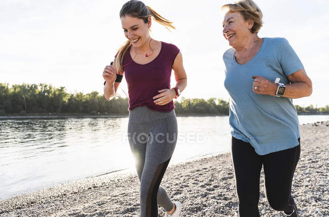 Nipote e nonna si divertono, facendo jogging insieme al fiume — Foto stock