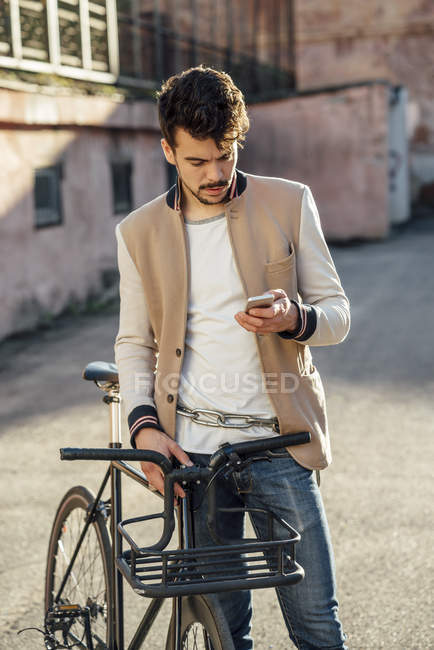 Young man with commuter fixie bike on a backyard in the city checking cell phone — Stock Photo