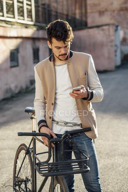 Молодой человек с пригородным велосипедом на заднем дворе в городе проверяет сотовый телефон — стоковое фото