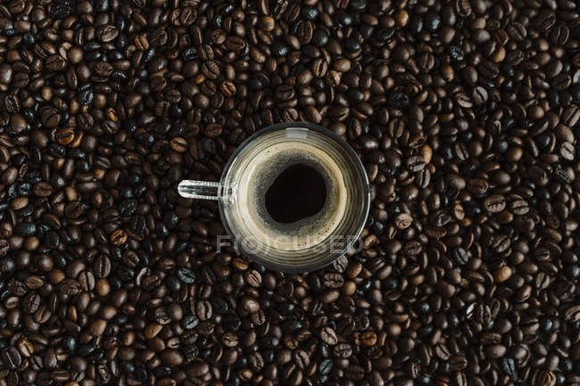 Glass of black coffee between coffee beans — стокове фото