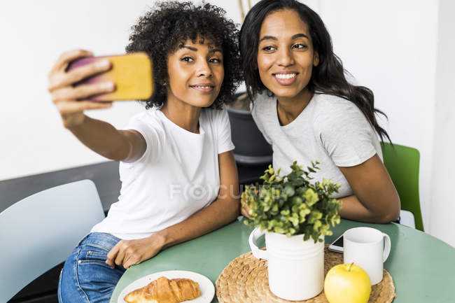 Дві щасливі дівчини, що сидять за столом і роблять селфі. — стокове фото