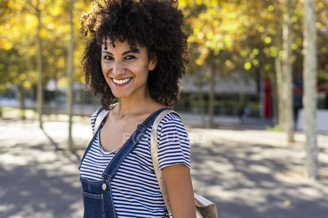 Portrait of a smiling woman, standing in a park — Stock Photo