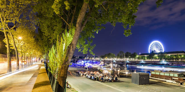 France, Paris, Champs-Elysées, Quai Anatole, les gens à la rive de la Seine la nuit — Photo de stock