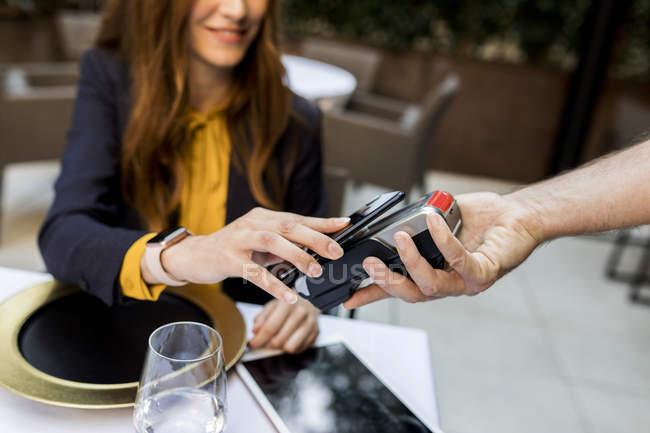 Donna che paga con smartphone in un ristorante — Foto stock