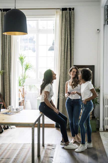 Trois femmes heureuses socialisant à la maison — Photo de stock