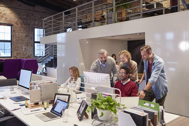 Colleagues looking over shoulder of young man working in modern office — Stock Photo