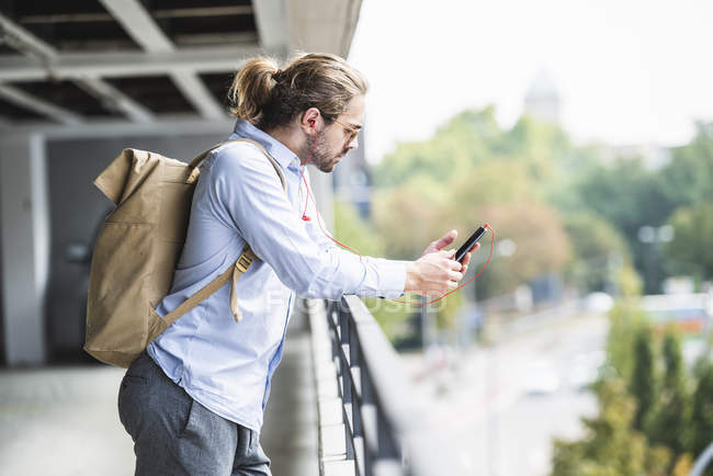 Young businessman with backpack standing in parking garage, using smartphone — Stock Photo