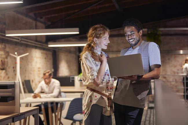 Мужчина в офисе держит ноутбук, разговаривает с коллегой — стоковое фото