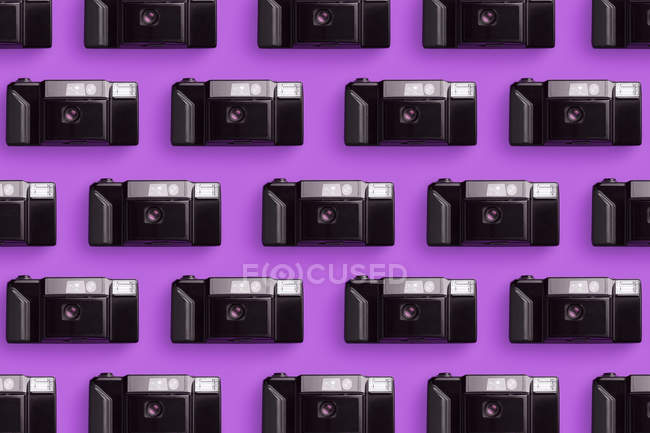 Plastic photo cameras organized in a row over pink background — Stock Photo
