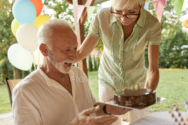 Woman handing over cake to happy husband on a garden party — Stock Photo