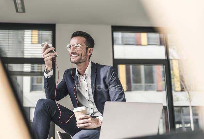 Бизнесмен разговаривает по телефону, используя наушники — стоковое фото