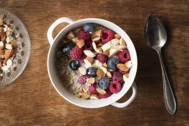 Cereales con leche de almendras, frutos secos y bayas, veganos - foto de stock