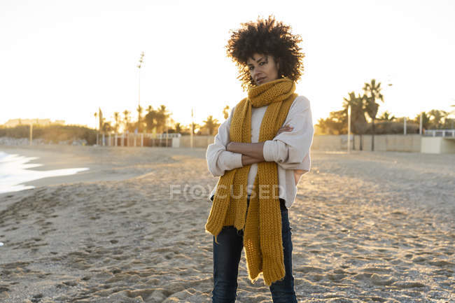 Cool woman standing on the beach with arms crossed — Stock Photo